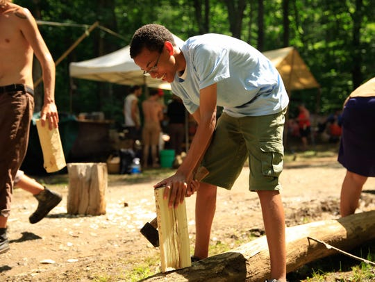 A young man learns to use a hatchet during a primitive