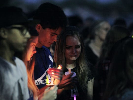 Students from Poudre High School mourn the loss of Wesley Strunk during the candlelight vigil at the Colorado State University Equine Center on June 27, 2017.