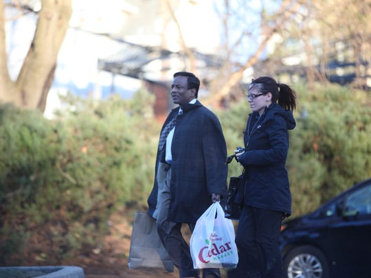 Dr. Gangaram Ragi walks towards his car on Mar. 17, 2015 beside an unidentified woman, from his Palisade Ave. office in Teaneck.