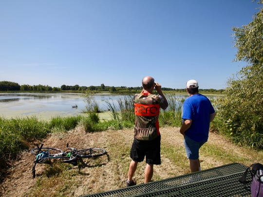 Mike Rhoades (left) and Paul Renaud look out over a wetland area on the Mascoutin Valley State Trail north of Ripon.