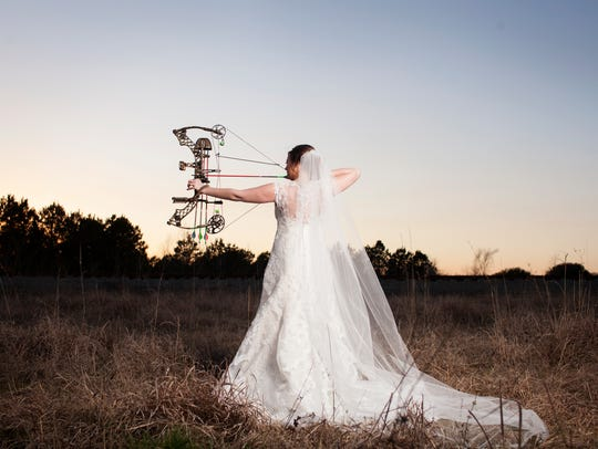 Lee Ann McQuillin aiming her bow in her wedding dress