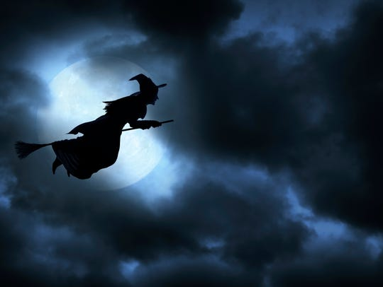 A witch flies on a broom on a spooky Halloween night.