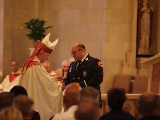 Gabriel Pabon Jr. (right) receives a plaque from Bishop Francis Malooly (left) to honor the passing of firefighter Ardythe Hope in October 2017.