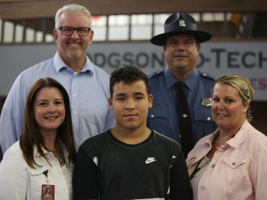 "Jaden Gray (bottom center) lost consciousness during class last week at Hodgson Vo-Tech.  Quick work from nurses Tracy McMullen (bottom left), Pam Diksa (bottom right) along with CPR from Detective Kevin Szymanski (top right) helped save his life.  Principal Jerry Lamey (top left) called the whole operation a ""team effort""."