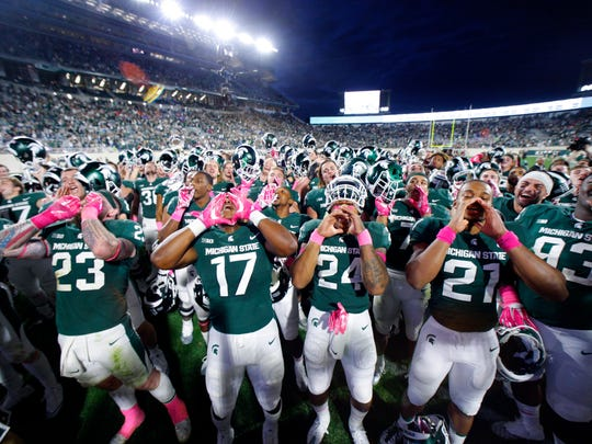 Michigan State players, including Chris Frey (23),