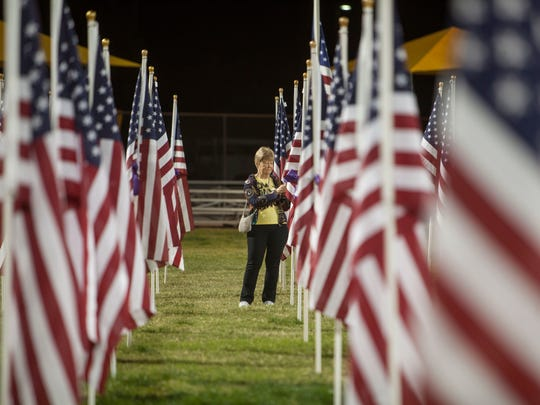 Friends and family of those affected by the Oct.1 shooting in Las Vegas, along with members of the surrounding community, visit the thousand flag dedication in Mesquite, Nev. Nov. 9, 2017. A portion of the flags are marked with photos and names of the victims.