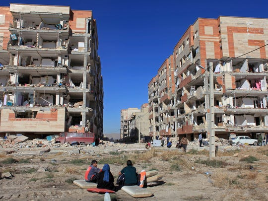Survivors sit in front of buildings damaged by an earthquake,
