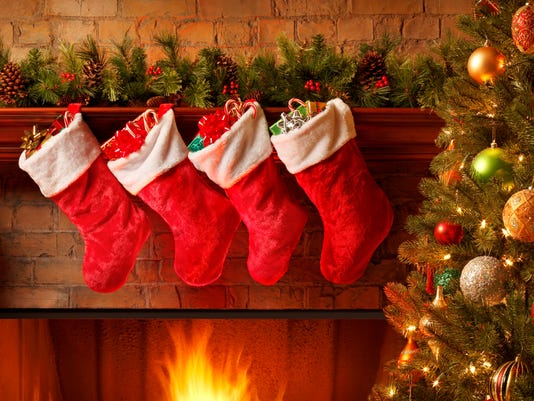 Christmas stockings hanging from a mantelpiece above glowing fireplace
