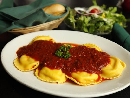 A dish of ravioli topped with the basil-rich signature