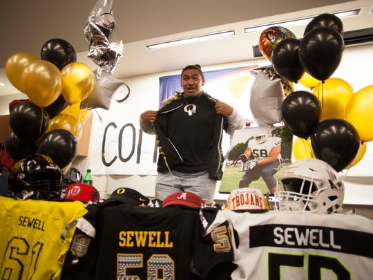 Penei Sewell, from Desert Hills High School, signs his letter of intent for the University of Oregon Wednesday, Feb. 7, 2018.