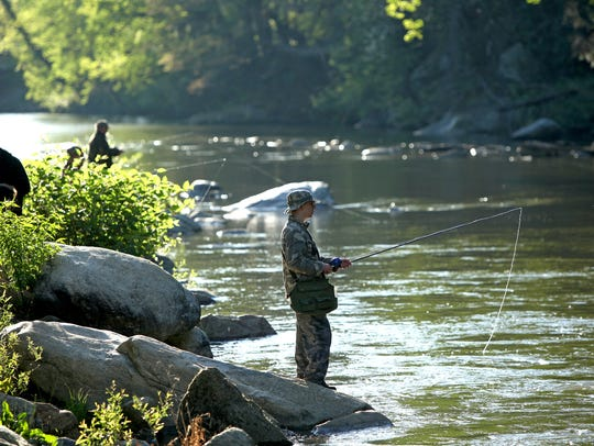 Fishermen line the Rocky Broad River in Bat Cave on a past opening day of hatchery-supported trout water fishing.