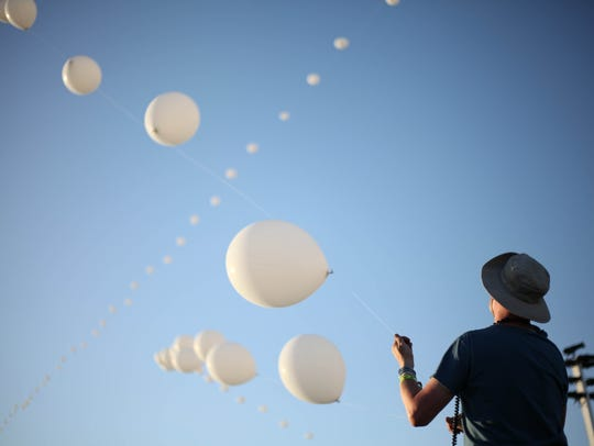 A man controls the iconic lines of balloons at the