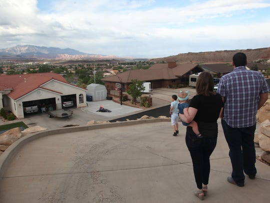 St. George couple Giovanni and Jennifer Trumbo and their two children look out from the driveway of a home they're trying to buy in Bloomington Hills on Thrusday, April 19, 2018.