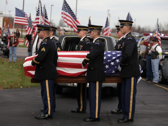 A military honor guard carries the remains of Vietnam