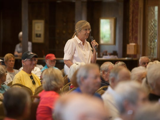 A woman asks a question during a forum with U.S. Senate