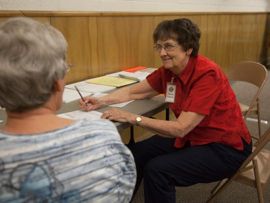 Lael Lovell helps votes fill out voter forms at the