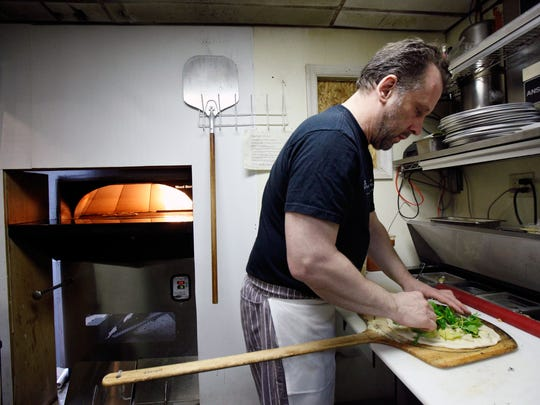 In this 2010 photo, Dave Weir, who then ran Buckley's Tavern in Centreville, cooks up a Black Olive and Margarita pizzas using a new authentic brick oven which weighed more than 4,000 pounds.