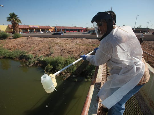 An employee of the California Regional Water Quality Control Board takes a water sample from the New River in Calexico, California.