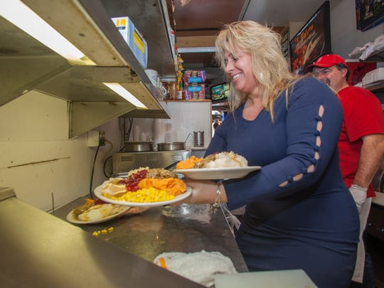 Jodi Davis and Jay Germani (owner) prep food for Pour House customers on Thanksgiving, Williston Road, South Burlington.  KEVIN HURLEY/for the Free Press