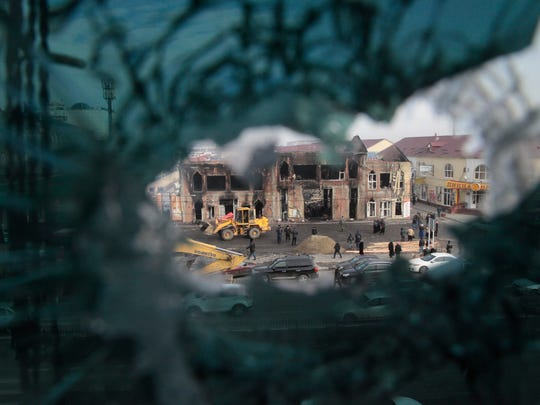 A burned-out market pavilion is seen through a bullet riddled broken window in central Grozny, Russia, Friday, Dec. 5, 2014.  Security forces in the capital of Russia's North Caucasus republic of Chechnya stormed two buildings yesterday, Dec. 4, including a school, during fierce gun battles with militants that left at least 19 dead, authorities said.