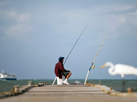 This Oct. 13, 2014 file photo shows a man fishing from a dock in Fajardo, Puerto Rico. In 2014, the Caribbean island saw the lowest number of homicides in nearly 15 years, part of a long-term trend of declining rates of violent crime across the region.