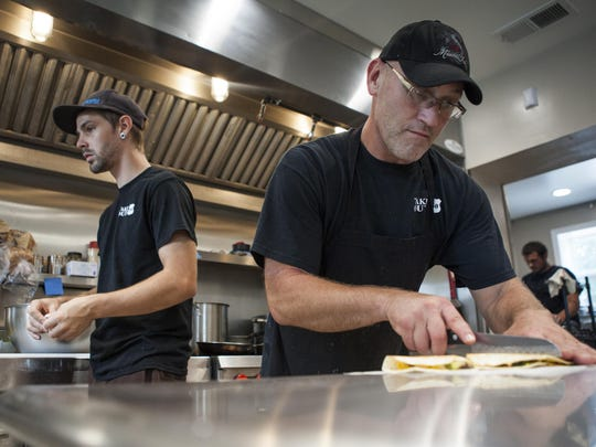 Chris Rose, a cook at Take Out 250 in Fishersville, cuts a cheeseburger quesadilla during lunch at the restaurant on Tuesday.
