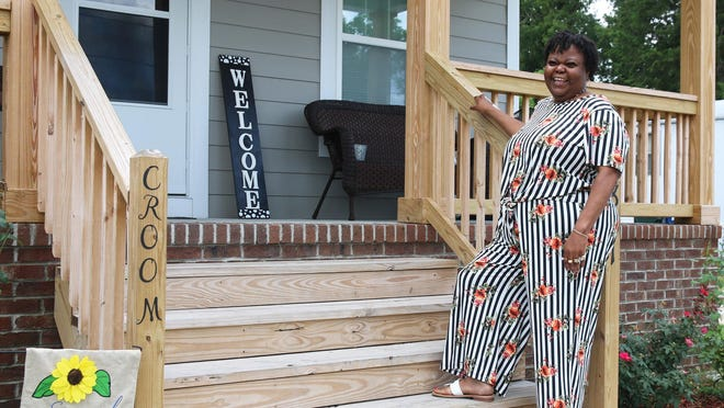 Antionette Croom stands on the front porch of her new home provided by ReBuild NC on Lincoln Street Saturday.