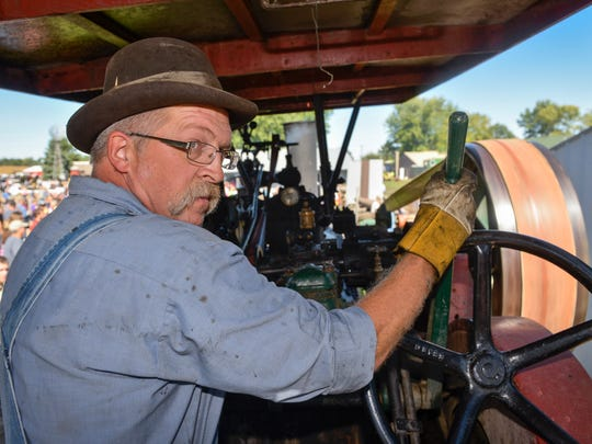 Frank Vouk stands at the controls of the steam engine