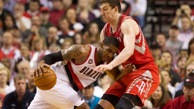 Portland Trail Blazers forward LaMarcus Aldridge (12) dribbles into Houston Rockets center Omer Asik (3) in the second half in game six of the first round of the 2014 NBA Playoffs at the Moda Center.