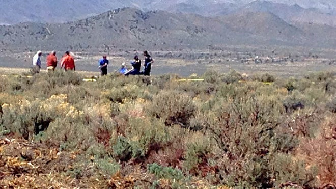 Authorities work at the scene of the crash of a small helicopter at Reno Stead Airport on Sunday.