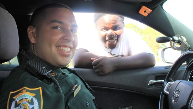 Indian River County Sheriff's Deputy Jonathan Lozada poses with Natron Young while on routine patrol in Gifford in this undated photo.