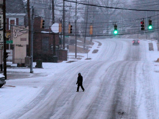 A pedestrian crosses Harrrison Avenue in Cheviot as snow begins cover area roads.