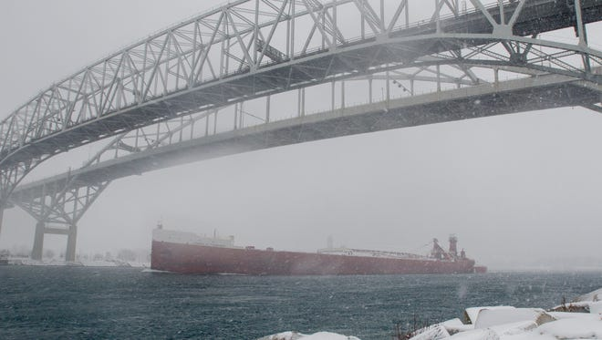 The Joseph H. Thompson heads north under the Blue Water Bridge Sunday, Dec. 11, through the snowy conditions in Port Huron.