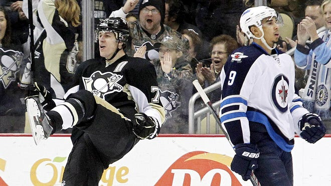 Pittsburgh Penguins center Evgeni Malkin kicks up his leg after scoring one of his two goals on Sunday against the Winnipeg Jets.