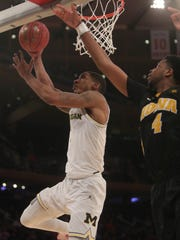 Charles Matthews scores against Iowa's Isaiah Moss during the second half Thursday.