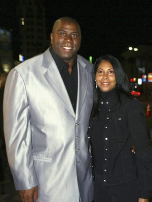 """Earvin """"Magic"""" Johnson and wife Cookie Johnson walks on the red carpet during MGM's premiere of """"Be Cool"""" at Grauman's Chinese Theatre on February 14, 2005 in Los Angeles, California."""