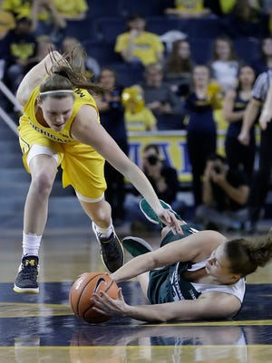 Michigan guard Nicole Munger, left, and Michigan State center Jenna Allen (33) chase the loose ball during the first half on Tuesday, Jan. 23, 2018, at Crisler Center.