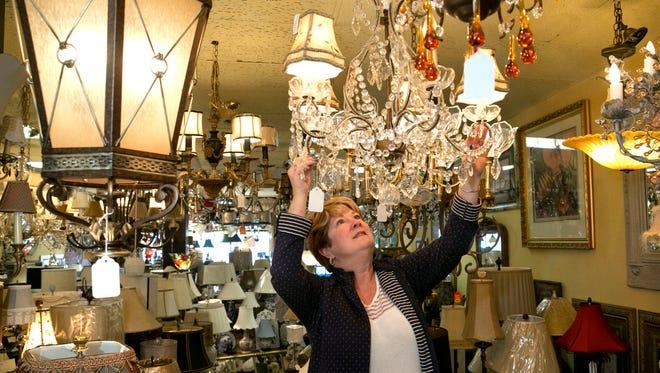 Dawne Howard, manager of Lavish Lighting in Shrewsbury, steadies a chandelier.