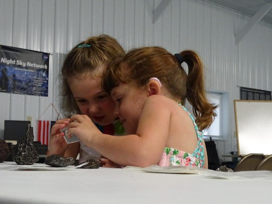 Five-year-old Lizzy Myers, right, and best friend Addison Schroeder, 4, explore various rocks during their visit to Warren Rupp Observatory. Myers' parents are helping her view the wonders of the world before a genetic condition takes her eyesight.