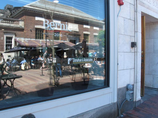 The Church Street Marketplace is reflected in the window of the building where Sen. Bernie Sanders' campaign headquarters is located in Burlington. Sanders is in Burlington for the weekend.