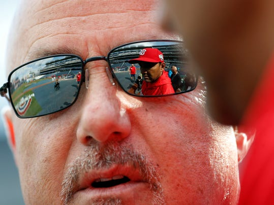 Washington Nationals general manager Mike Rizzo speaks with manager Dave Martinez, seen in Rizzo's sunglasses, before the home opener baseball game against the New York Mets at Nationals Park, Thursday, April 5, 2018, in Washington. (AP Photo/Alex Brandon)