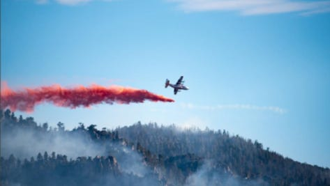 A firefighting plane drops retardant over the Saddle Fire on Wednesday. The fire, located near the Washington County community of Pine Valley, had grown to more than 900 acres on Thursday.