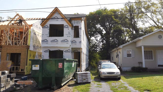 """Construction crews work on a pair of homes in East Nashville. Two """"tall skinny"""" homes can be built on one lot when they are six feet apart, among other conditions."""