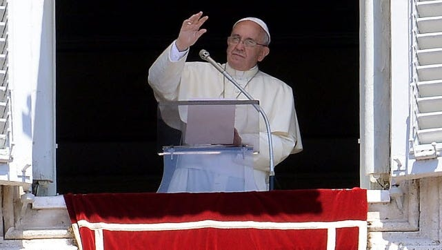 Pope Francis waves from the window of his study overlooking St. Peter's Square at the Vatican on July 6.