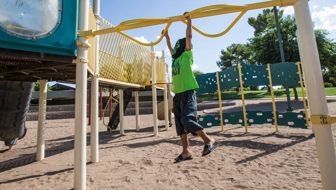 Dominic Trevino hangs while he plays with his brother at Dobson Ranch Park playground on August 28, 2016 in Mesa, Arizona.
