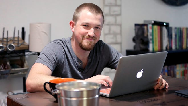 In this Wednesday, May 18, 2016, photo, Mitchell Timme works from his laptop computer at his home in Phoenix.
