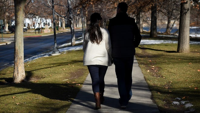 Jose Gastelum-Cardenas and his wife, Arlene Torres, hold each other while posing for a portrait next to the Truckee River near downtown Reno on Friday.