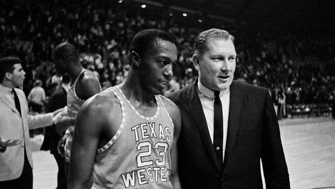 Texas Western Coach Don Haskins, right, escortsed Orsten Artis off the court after the Miners came out on top in the NCAA semi-final game with Utah at the University of Maryland, March 19, 1966, College Park, Md. Texas western won 85-78 with Artis leading his teammates with 22 points.