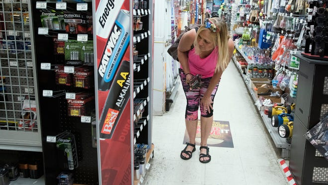 Paula Gil searches for batteries on Tuesday, Sept. 5, 2017, at Hall's Hardware and Lumber in Milton as residents brace for Hurricane Irma.
