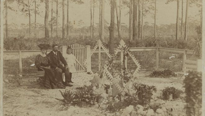"Nick Armeda; his wife, Josephine; and their daughter, Theresa, at the grave of their 3 1/2-month-old infant, Ambrose, in 1904 at the Fort Myers Cemetery.  Says granddaughter, June Johnson, 88, ""The cemetery was far out of town back then. Big Mama always said she felt like she'd left her baby way out in the woods."""